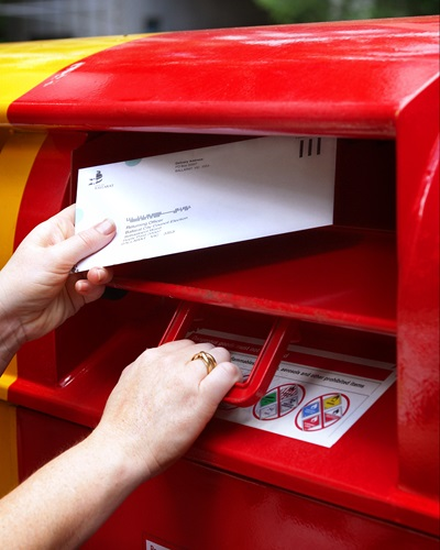 Image of hand putting letter in postbox
